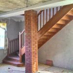 Установлена деревянная лестница с забежными ступеньками в повороте с ограждением и балюстрадой на втором этаже.